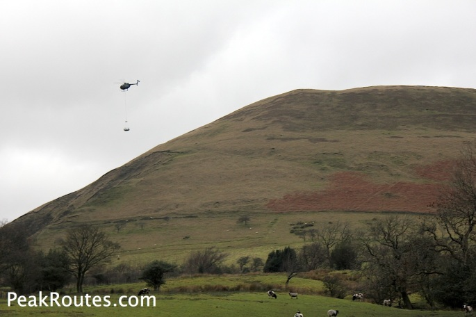 Helicopter carrying supplies past Broadlee-Bank Tor